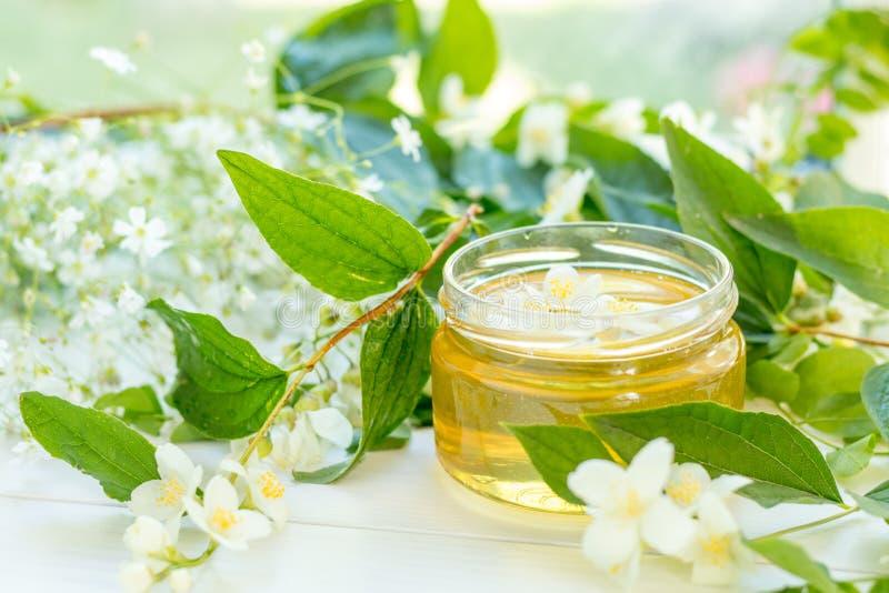 Honey in glass jars. With jasmine flowers on windowsill. Shallow depth of field stock image