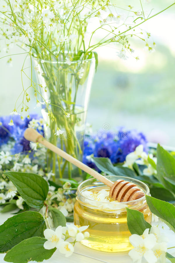 Honey in glass jars. With jasmine flowers on windowsill. Shallow depth of field royalty free stock photography
