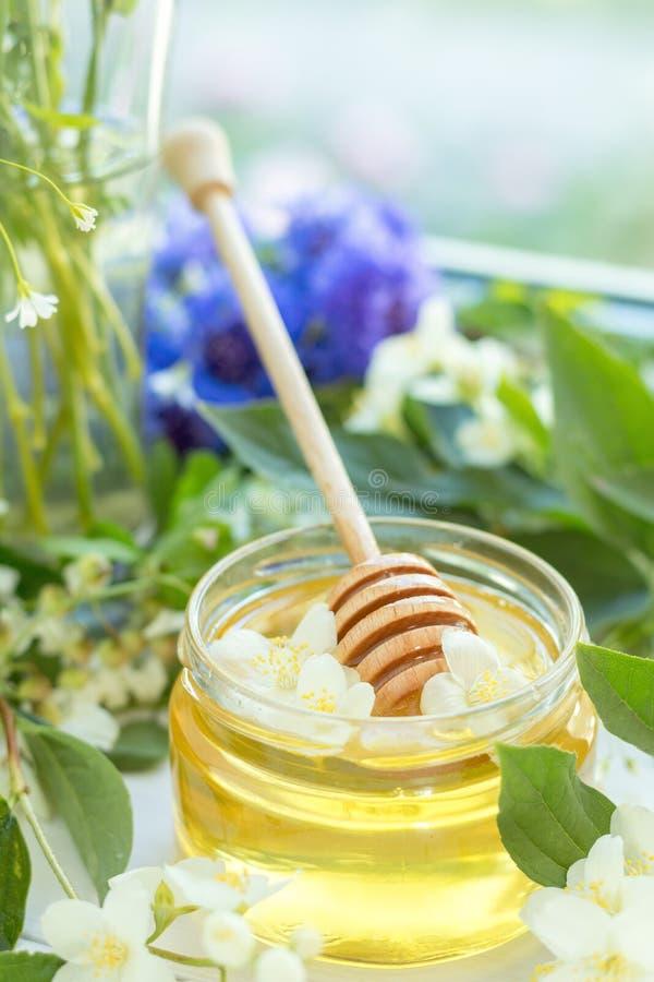 Honey in glass jars. With jasmine flowers on windowsill. Shallow depth of field stock photo