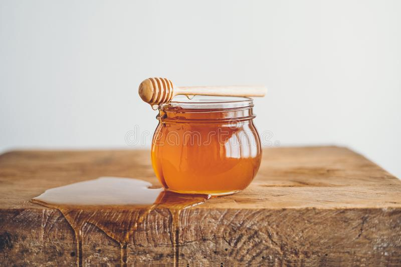 Honey in a glass and Honey scoop White background stock photography