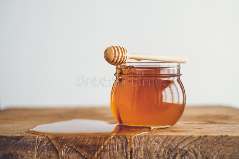 Honey in a glass and Honey scoop White background stock photo