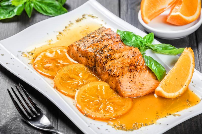 Honey Glazed fillet salmon with orange slices, spices and basil on white plate on dark background. Delicious dish of seafood stock photos