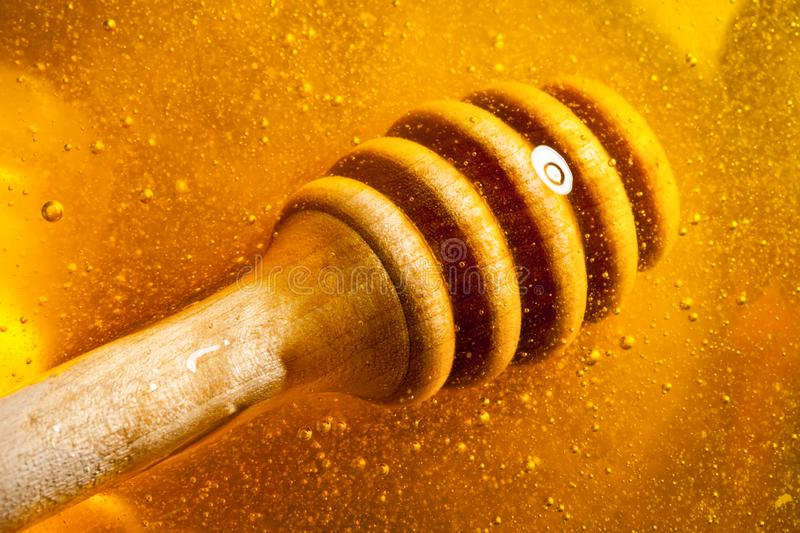 Honey with gold color flows down from a spoon. Healthy food concept. Healthy eating. Diet. Selective focus. Background. Honey with gold color flows down from a royalty free stock photo