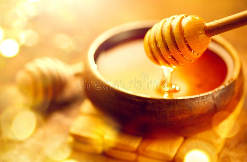 Honey. Healthy organic thick honey dripping from the honey dipper in wooden bowl. Sweet dessert. Background royalty free stock image