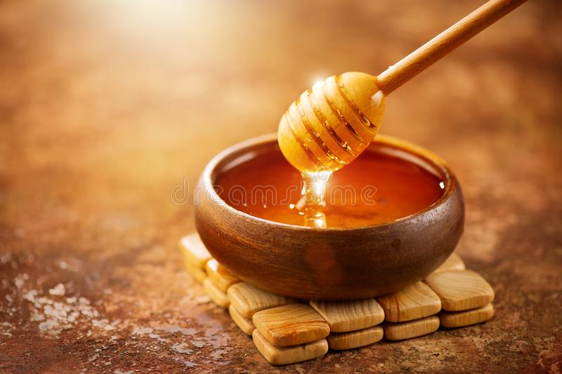 Honey. Healthy organic thick honey dripping from the honey dipper in wooden bowl. Sweet dessert stock photos
