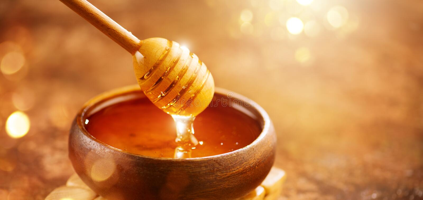 Honey. Healthy organic thick honey dripping from the honey dipper in wooden bowl. Sweet dessert. Background stock photo