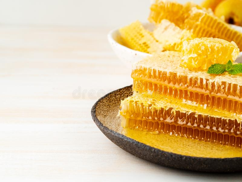 honey in honeycomb, close-up, on brown ceramic plate, on wooden royalty free stock photography