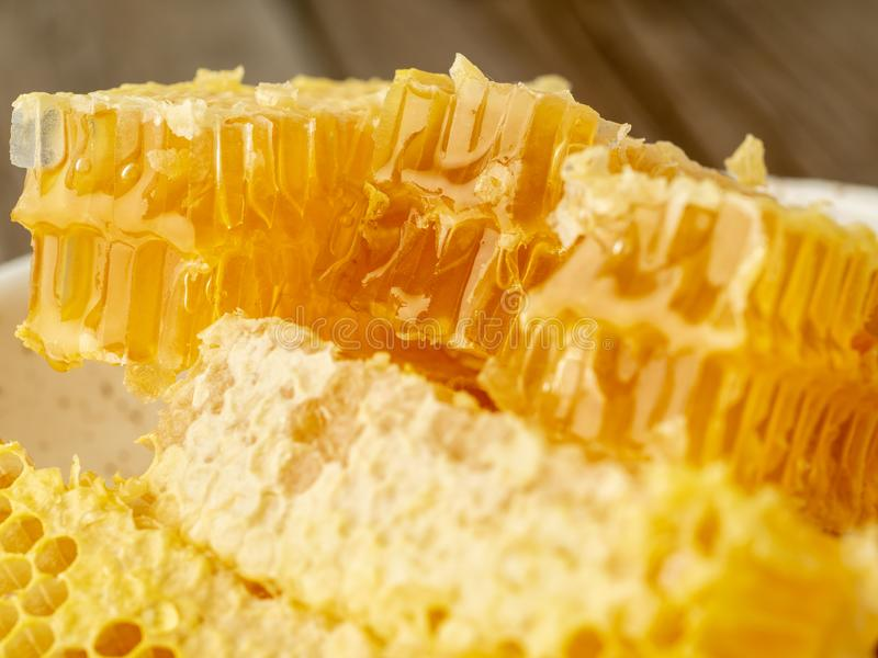 Honey in honeycomb, close-up, on white ceramic plate, on wooden royalty free stock photos