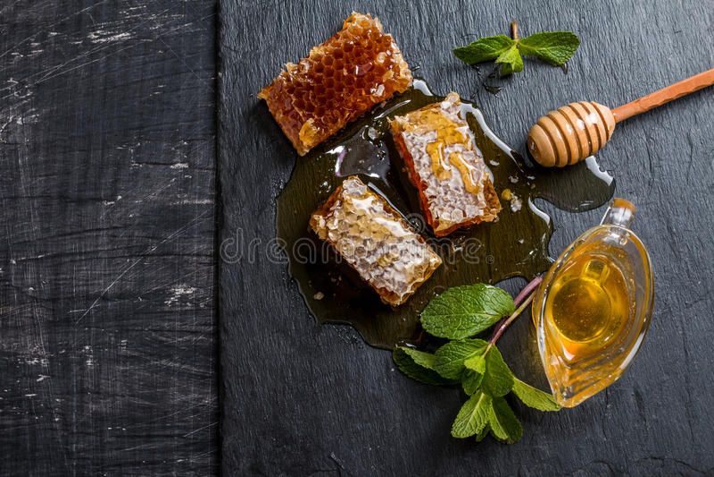 Honey, honeycomb, mint and honey dipper royalty free stock image