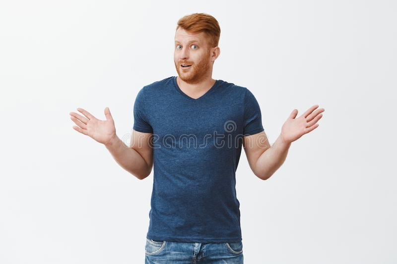 Honey, I have no idea who is she. Portrait of confused and clueless friendly-looking masculine husband with red hair and. Bristle, shrugging with raised palms stock photo