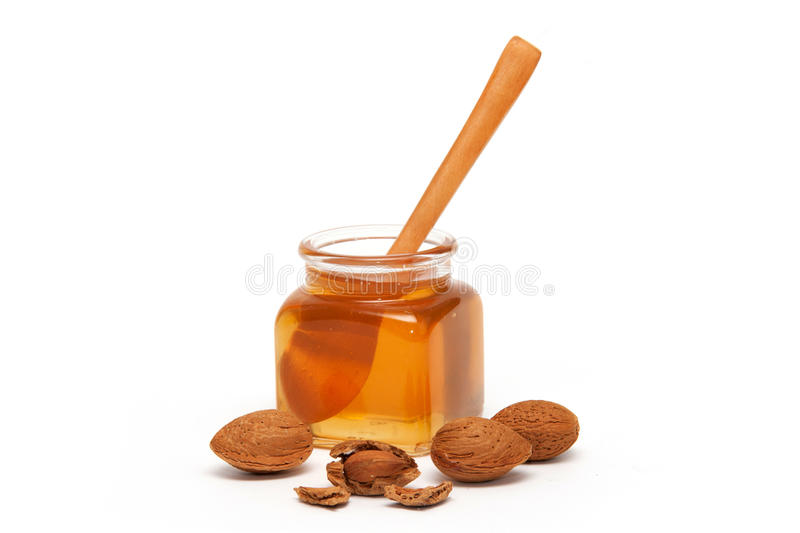 Honey in the jar and almonds. Isolated on white royalty free stock photography
