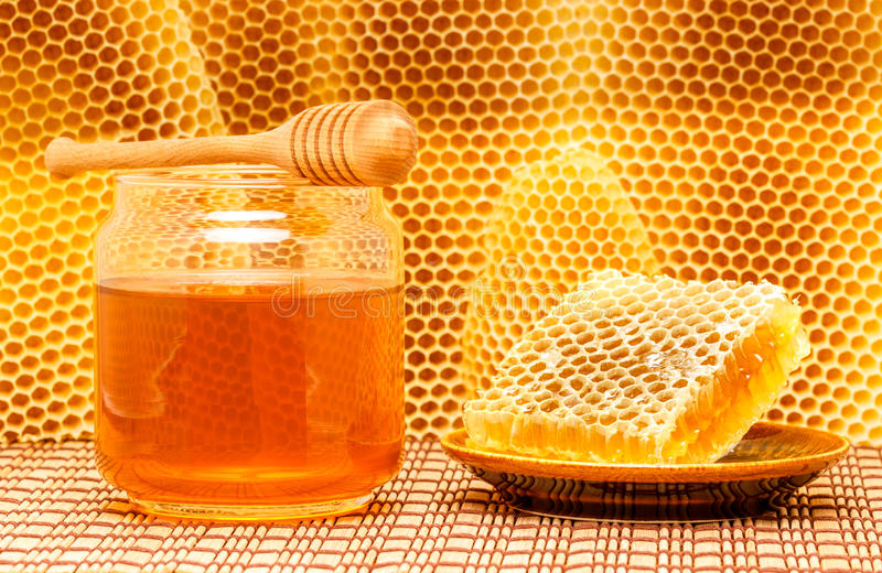 Honey in jar with dipper and honeycomb on mat stock photo
