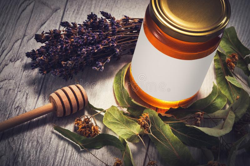 Honey in jar with honey dipper and lavender and linden flowers on vintage wooden background stock photos