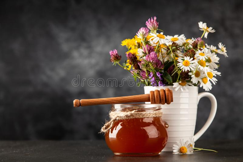 Honey jar and dipper. With leaking honey royalty free stock image