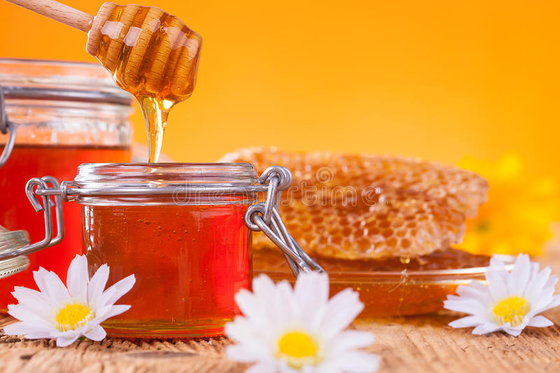 Honey in jar with honeycomb and wooden drizzler. Still life of honey on wooden table stock photos