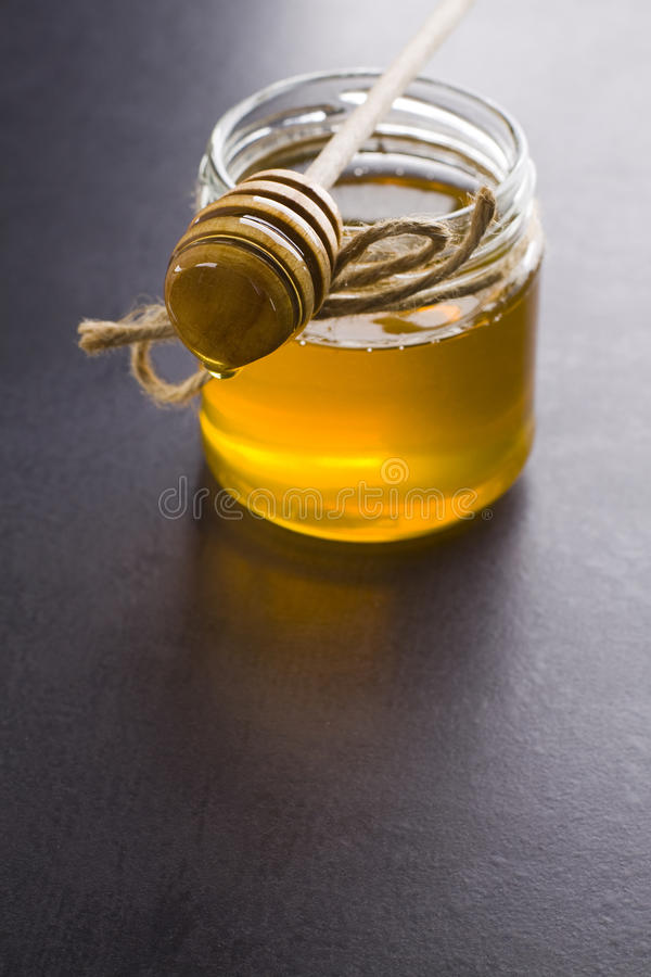 Honey. Jar of honey with the scoop stock photos