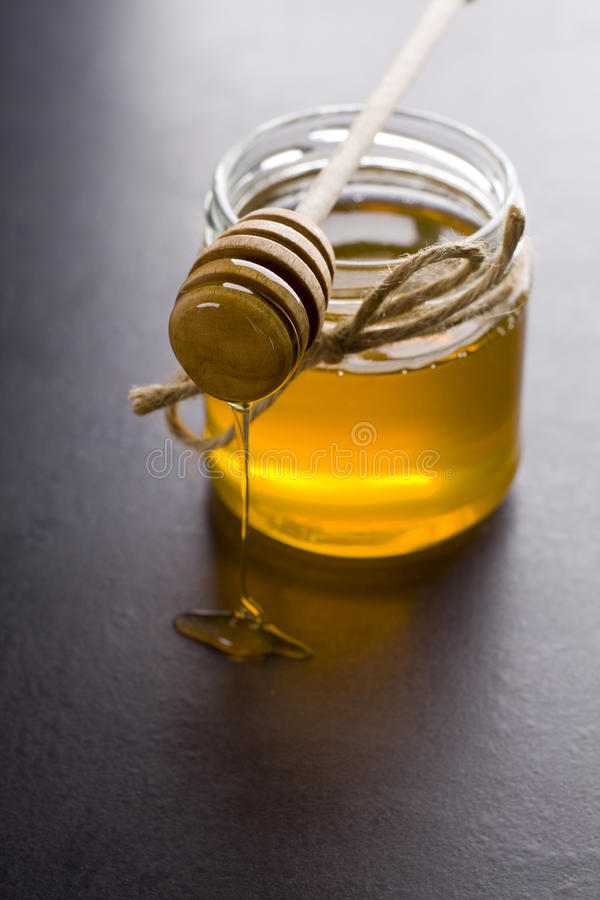 Honey. Jar of honey with the scoop royalty free stock photography