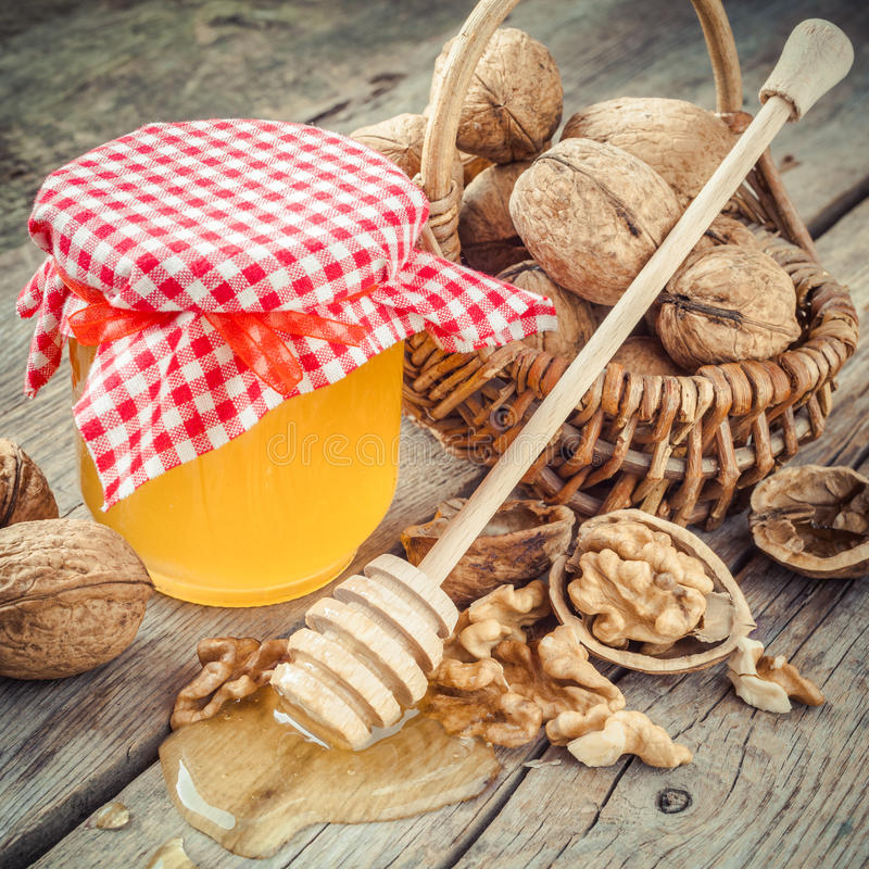 Honey in jar, walnut in basket and wooden dipper on old kitchen. Table royalty free stock photo