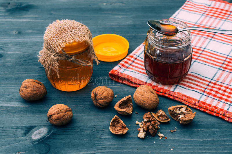 Honey in a jar with walnuts on a blue wooden table. Walnut in the shell. stock photography