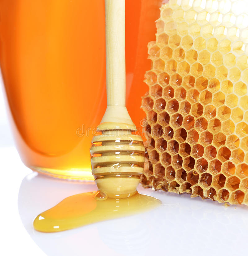 Honey jar. Jar of wild honey with a wooden dripper. Isolated on white background royalty free stock images