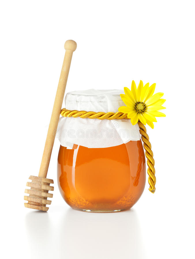 Honey jar with wooden dripper. Jar of honey with wooden dripper and yellow flower, isolated on white background stock image
