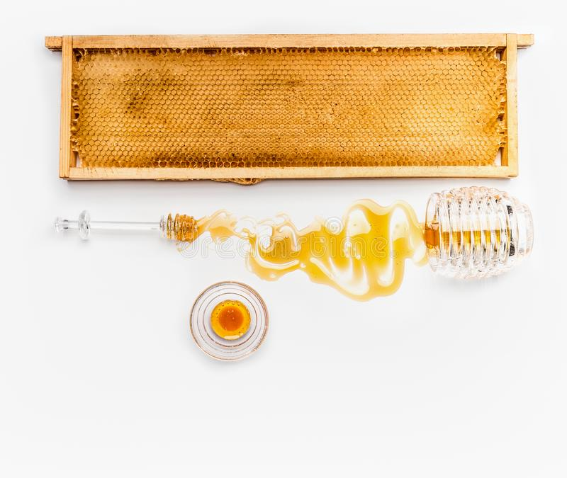 Honey in jars with dipper, honeycomb frame and wild flowers on white background, top view. Healthy food royalty free stock photography