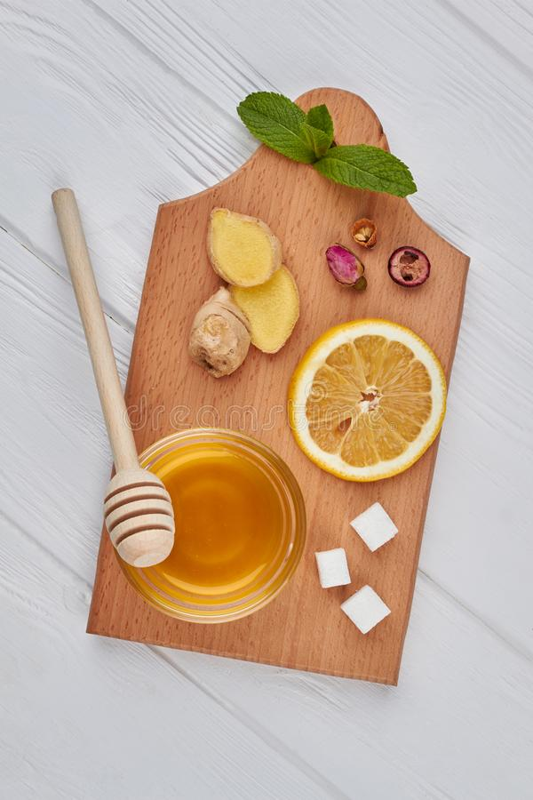 Honey, lemon and ginger on cutting board. Ingredients for healthy tea, top view. Concept of morning breakfast. Flat lay composition royalty free stock photo