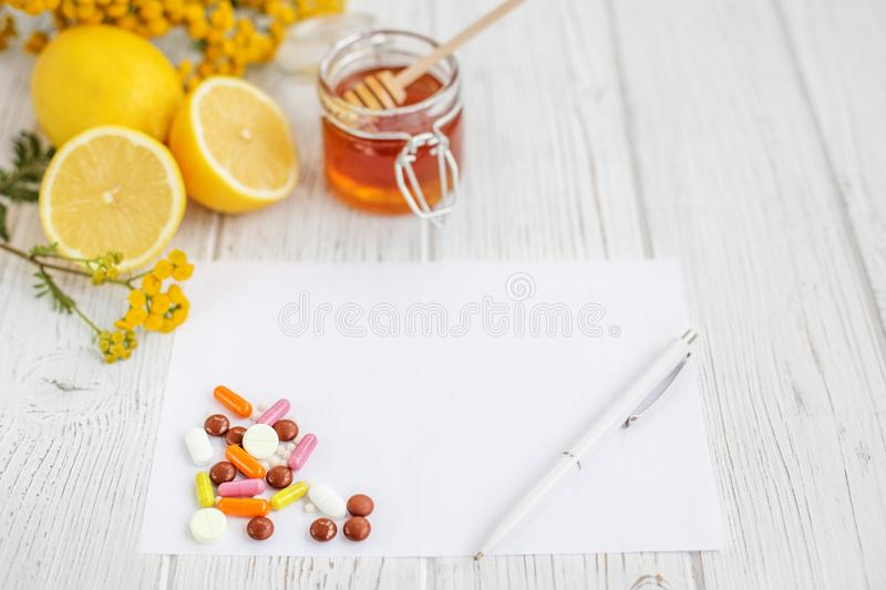 Honey and lemon. Many pills. Letter to the recipe and pen. Conce stock photo