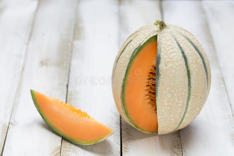 Honey melon cut open on white wooden background royalty free stock images