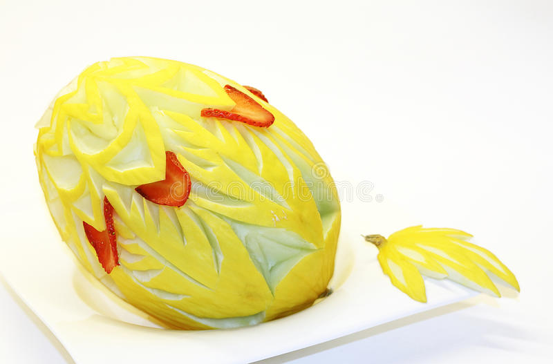 Honey melon with ornate decoration. Garnished honeydew melon on a white plate stock image