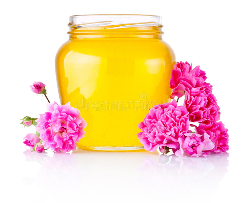 Honey in open glass jar and flowers isolated on white background stock photo