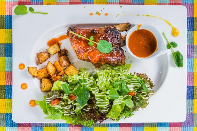 Honey Pork Ribs Served met Salade en Kruidige Saus in Witte Plaat op Kleurrijke Lijst stock afbeelding