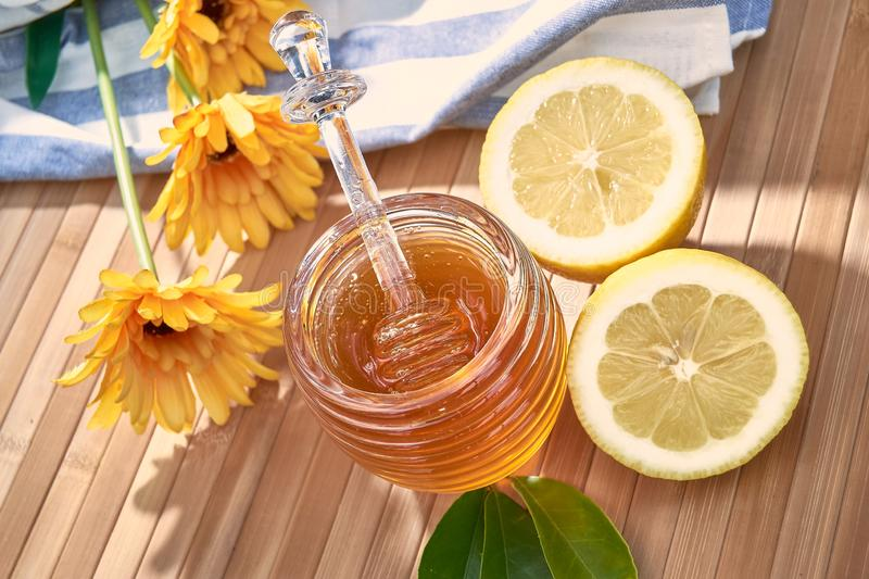Honey pot on bamboo wood. With plastic daisies and lemons cut in half in the middle of the field sweet honeycomb dipper natural healthy stick delicious nature stock images