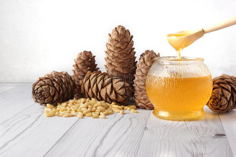 Honey is poured from a wooden spoon into a glass barrel, next to cedar cones and nuts on a light background royalty free stock image