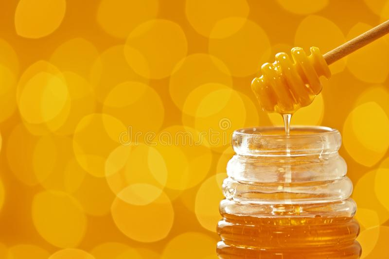 Honey pouring from dipper into jar on blurred background. royalty free stock photos