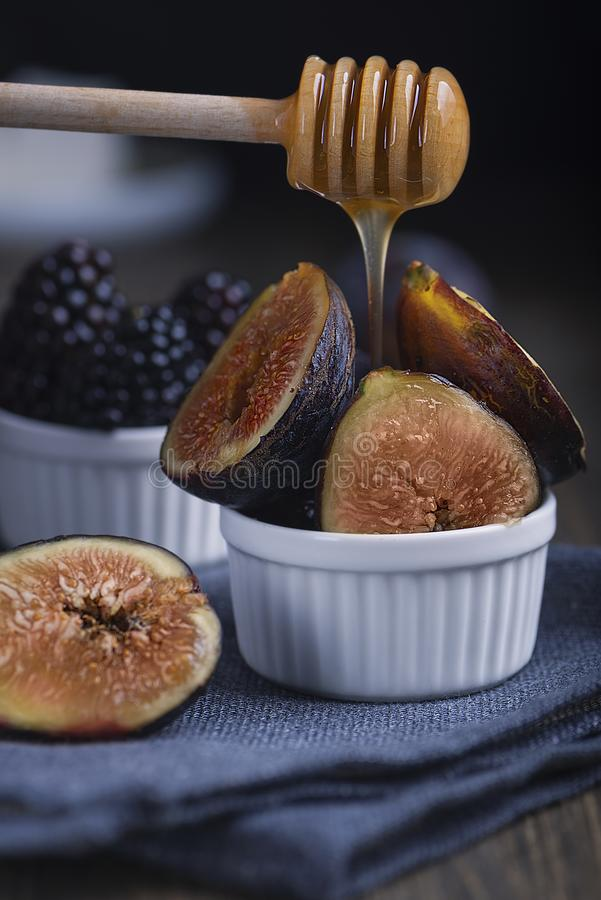 Honey pouring of fresh cuted organic figs and blackberry on white cupcake baking dishes on rustic wooden background with dark blue stock images