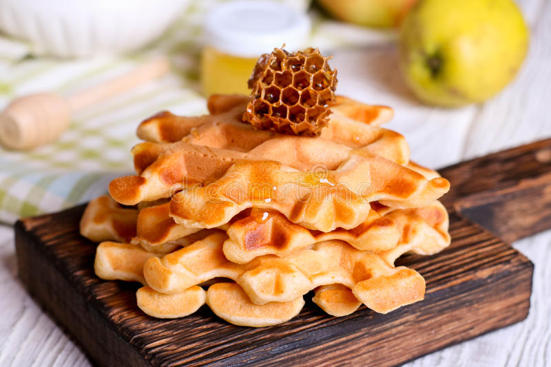 Honey pouring on a fresh waffles. Breakfast with Belgian waffles. Close up, horizontal stock photos