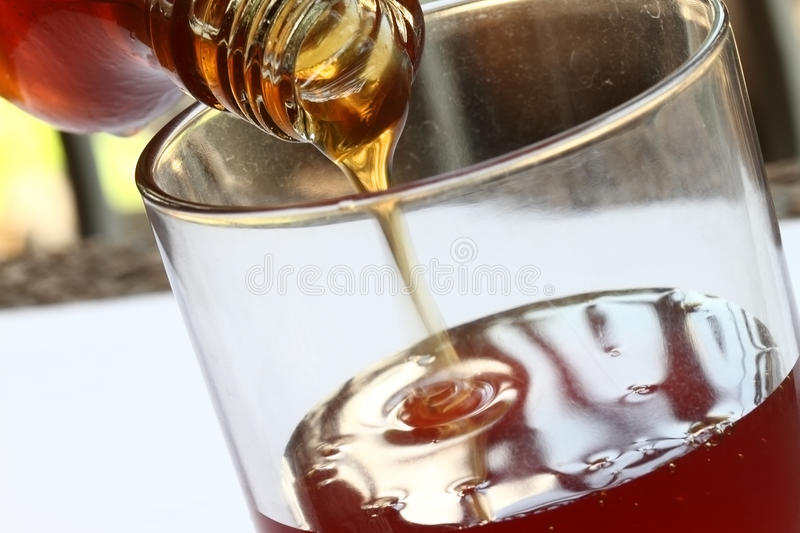Honey Pouring From Jar Stock Photos