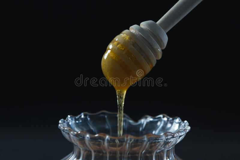 Honey pouring into a jar. Against black background royalty free stock photo