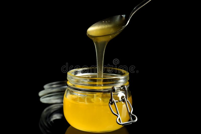 Honey pouring from metal spoon in glass jar against dark background stock photos