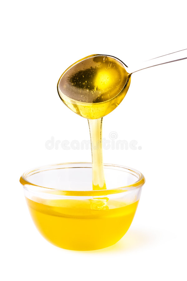 Honey pouring from the spoon royalty free stock photo