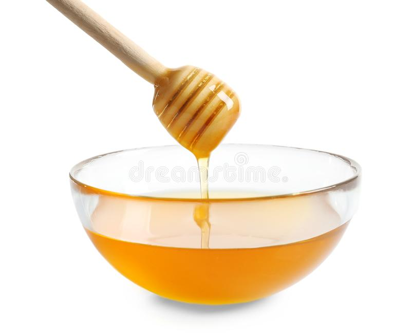 Honey pouring from wooden honey dipper into glass bowl royalty free stock images