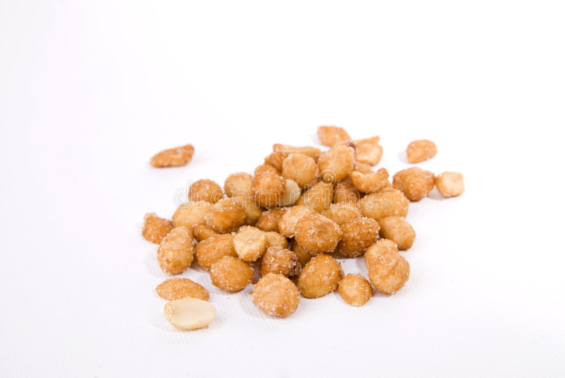 Honey roasted peanuts. Many honey roasted peanuts on a white background stock photo