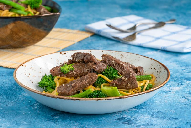 Honey and sesame beef noodles with green vegetables royalty free stock images