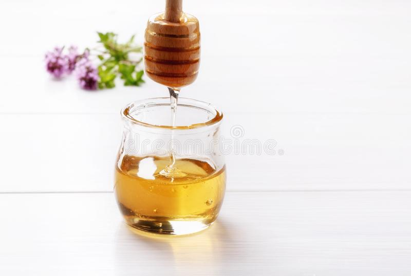 Honey in a small glass jar on a white table Honey dripping from dipper royalty free stock photo