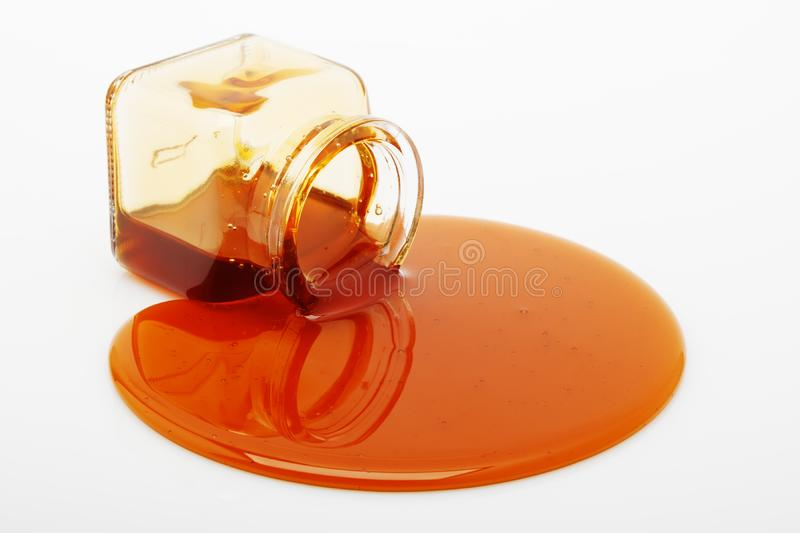 Honey spill from a glass jar. On white stock image