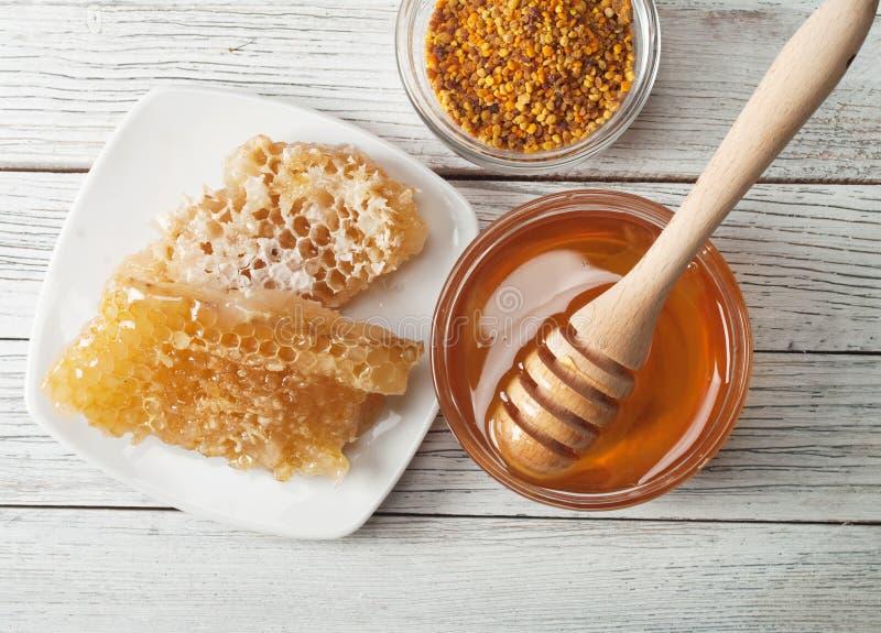 Honey. Still life with honey, honeycomb, pollen royalty free stock image