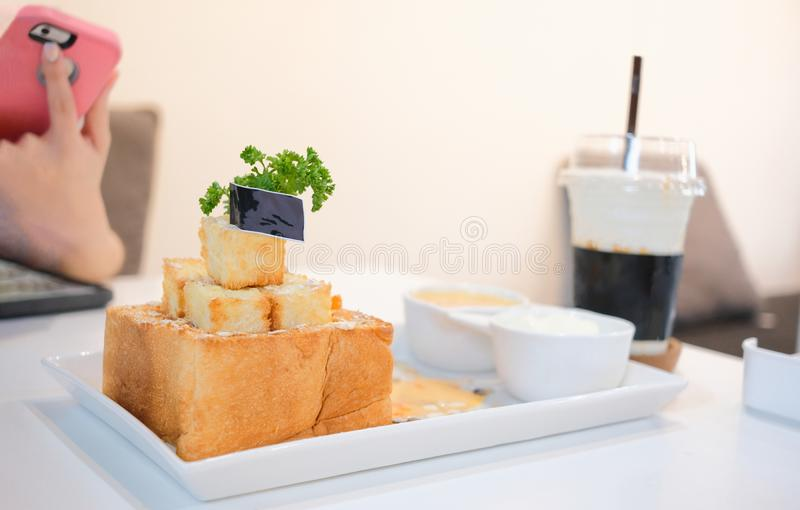 Honey toast with salted egg sauce and ice-cream and girl take picture before eat. Set of dessert foods and drink at the c. Close up honey toast with salted egg stock photos