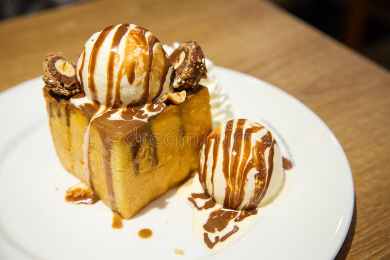 honey toast with vanilla ice cream and whiping cream topped with chocolate sauce on white dish. stock photography
