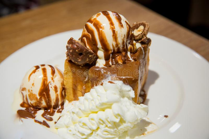 Honey toast with vanilla ice cream and whiping cream topped with chocolate sauce on white dish. stock photos